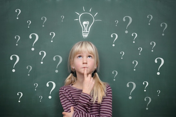 Schoolgirl at the Blackboard with Question Marks and Idea